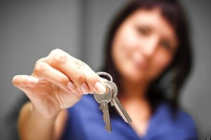 CE53T4 Realtor is giving the keys to an apartment to some clients. focus on the keys